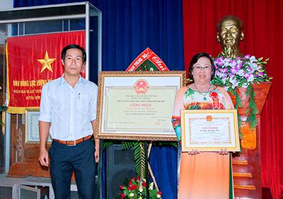 Cô Hoa chụp ảnh lưu niệm cùng với tấm bằng chứng nhận của Xã Diên Phú